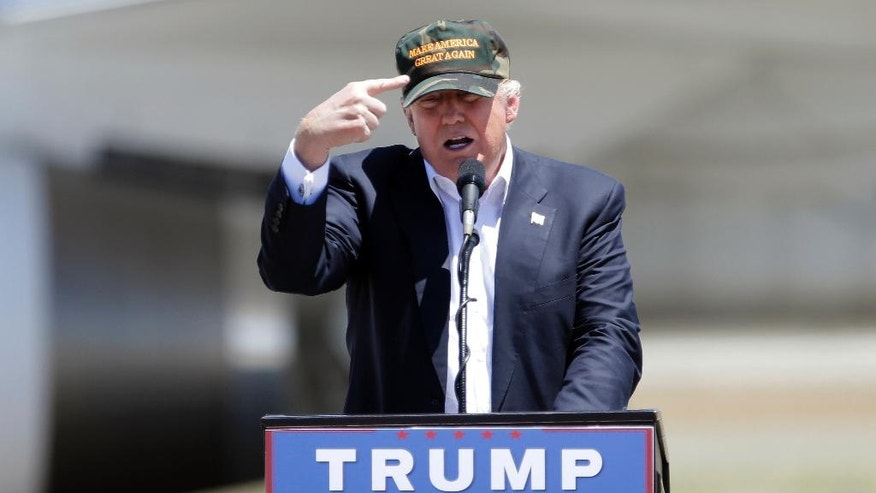 """FILE - In this June 3, 2016 file photo, Republican presidential candidate Donald Trump gestures to a his camouflaged """"Make America Great"""" hat at a campaign rally at the Redding Municipal Airport in Redding, Calif.  Trump's prediction that he can win California in the November presidential election challenges the dismal history for Republican nominees in one of the nation's Democratic strongholds. (AP Photo/Rich Pedroncelli)"""