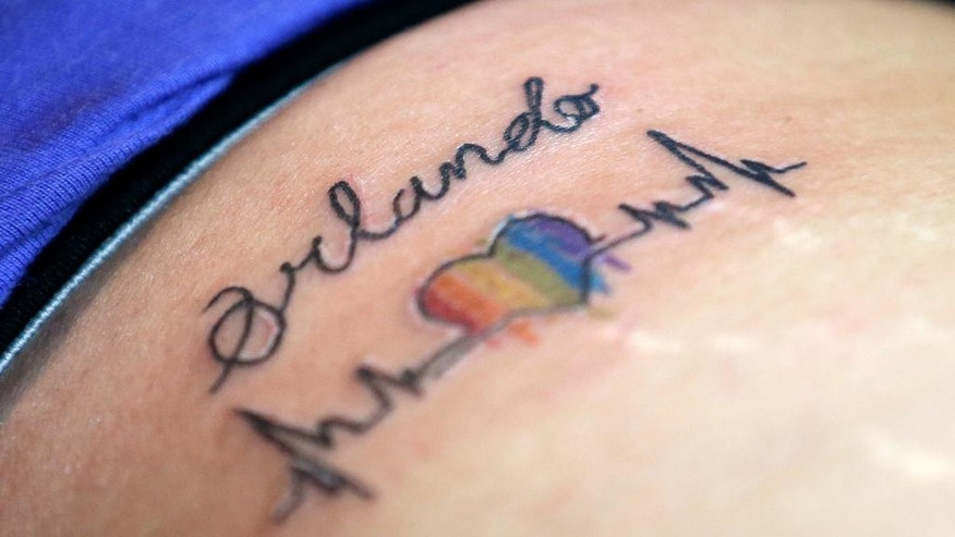 A tattoo showing solidarity with Orlando Pulse is seen on a customer at the Stigma Tattoo parlor, Saturday, June 18, 2016, in Orlando, Fla. Tattoo artists donated their time to draw various designs, and all proceeds will be donated to the victims of the Pulse nightclub mass shootings. (AP Photo/John Raoux)