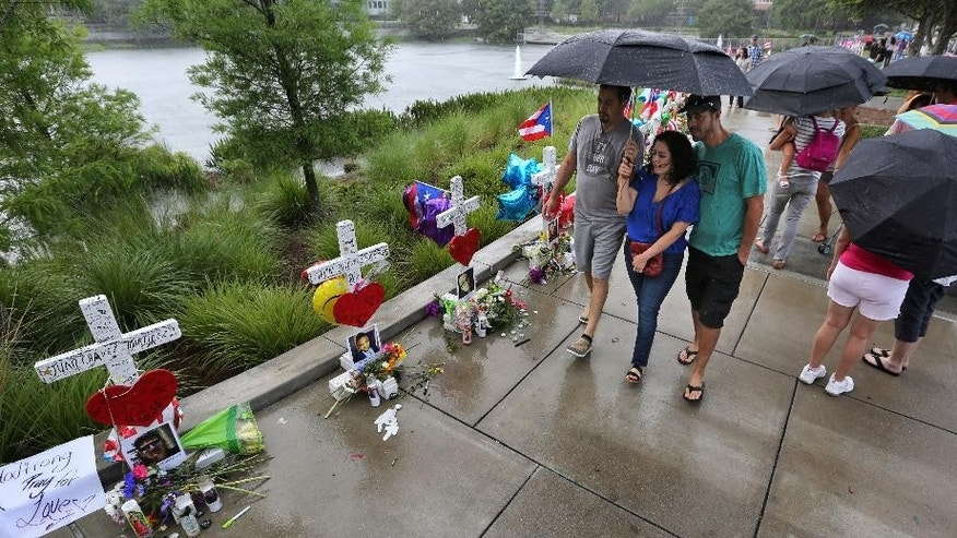 Visitors brave the rain to view the 49 crosses at  the makeshift memorial outside Orlando Regional Medical Center, Sunday, June 19, 2016. The crosses were erected by an Illinois man to honor each of the victims in the Pulse massacre. (Joe Burbank/Orlando Sentinel via AP)