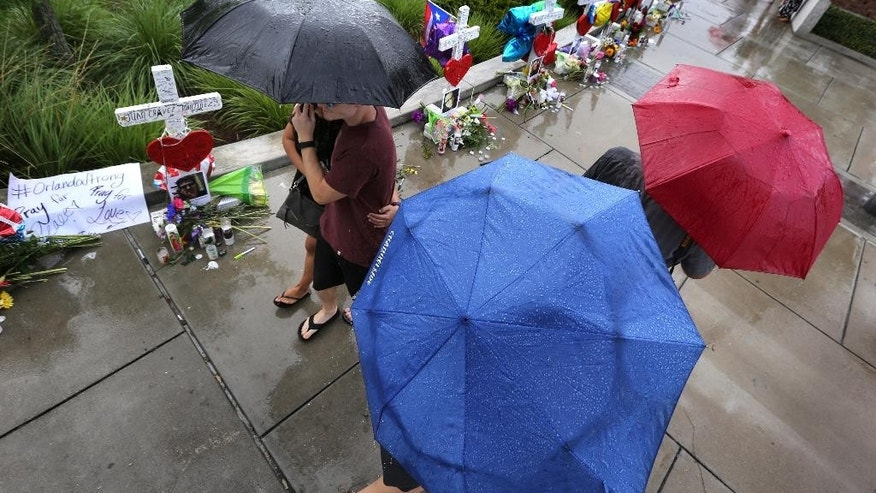 Visitors brave the rain to view the 49 crosses at a makeshift memorial outside Orlando Regional Medical Center, Sunday , June 19, 2016. The crosses were erected by an Illinois man to honor each of the victims in the Pulse massacre. (Joe Burbank/Orlando Sentinel via AP)