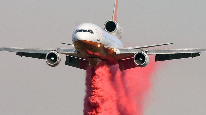 A McDonnell Douglas DC-10 belonging to Tanker10 Aviation makes a Phos-Chek drop Saturday, June 18, 2016, on wildfires in Santa Barbara County, Calif. (Mike Eliason/Santa Barbara County Fire Department via AP)