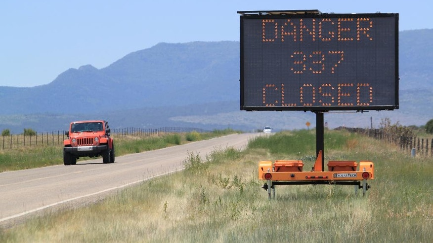 Travelers are warned about road closures along the Manzano Mountains near Tajique, N.M., on Friday, June 17, 2016. A wildfire burning to the north had charred more than 26 square miles after starting earlier this week, forcing evacuations and destroying an estimated 24 homes. (AP Photo/Susan Montoya Bryan)