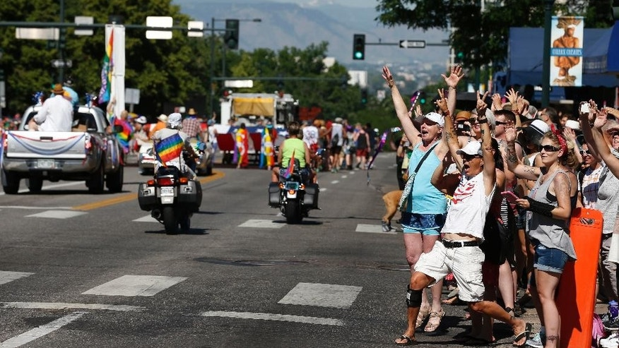 A crowd cheers for participants in the gay pride parade in Denver, Sunday June 19, 2016. (AP Photo/Brennan Linsley)