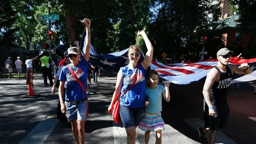 U.S. Army veteran Sarah Alder, left, her partner Joyce McCall, second from left, and their daughter Lydia help carry a giant American flag in the gay pride parade, in Denver, Sunday, June 19, 2016. (AP Photo/Brennan Linsley)