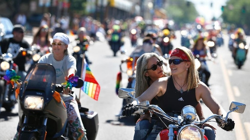 Participants in the gay pride parade ride mototcycles, in Denver, Sunday, June 19, 2016. People in wheelchairs, walking on stilts and riding rainbow-decorated motorcycles turned out for gay pride events over the weekend, including people on parade in Denver carrying posters of the names or faces of the victims who died in last weekend's attack on a gay nightclub in Florida. (AP Photo/Brennan Linsley)