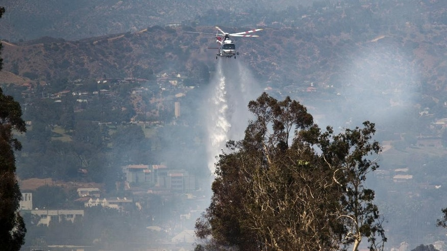 Firefighters douse a fire under State Route 2 after a brush fire swept through threatening homes in Los Angeles on Sunday, June 19, 2016. Los Angeles firefighters say they have contained the fire in the densely populated neighborhood along a freeway. (AP Photo/Damian Dovarganes)