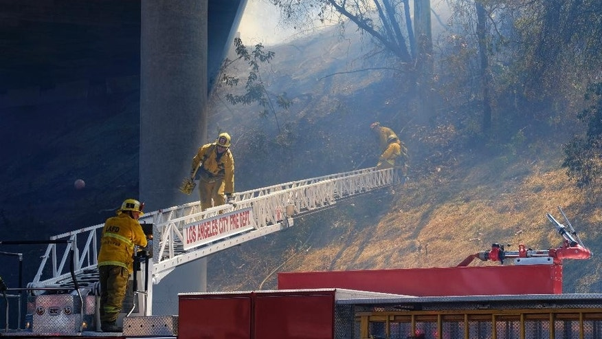 A firefighters climbs down a ladder along a hillside under State Route 2 after a brush fire swept through threatening homes in Los Angeles on Sunday, June 19, 2016. Los Angeles firefighters say they have contained the fire that was in a densely populated neighborhood along a freeway. (AP Photo/Richard Vogel)