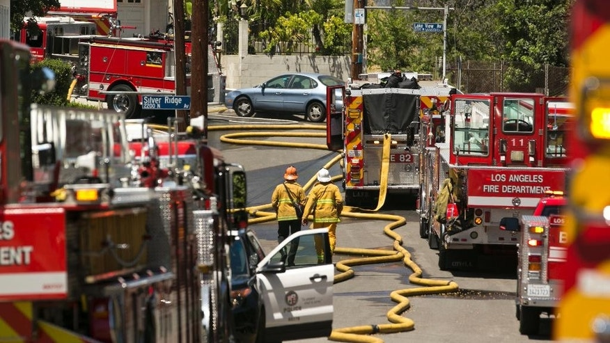 Los Angeles Fire Department trucks are deployed on a densely populated neighborhood after a brush fire swept through threatening homes in Los Angeles on Sunday, June 19, 2016. (AP Photo/Damian Dovarganes)