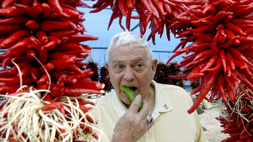 FILE - In this Aug. 30, 2008 file photo, framed by ristras, John Trewitt bites into a pod of fresh Hatch green chile, at the Hatch Chile Festival in Hatch, N.M.