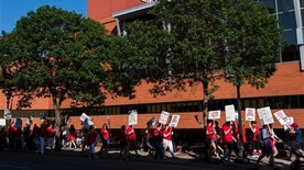 Picketers walk in front of United Hospital in St. Paul, Minn., Sunday, June 19. 2016. About 4,800 nurses at five Minneapolis-area hospitals, all operated by Allina Health, began a weeklong strike Sunday over a contract impasse. (Isaac Hale /Star Tribune via AP)