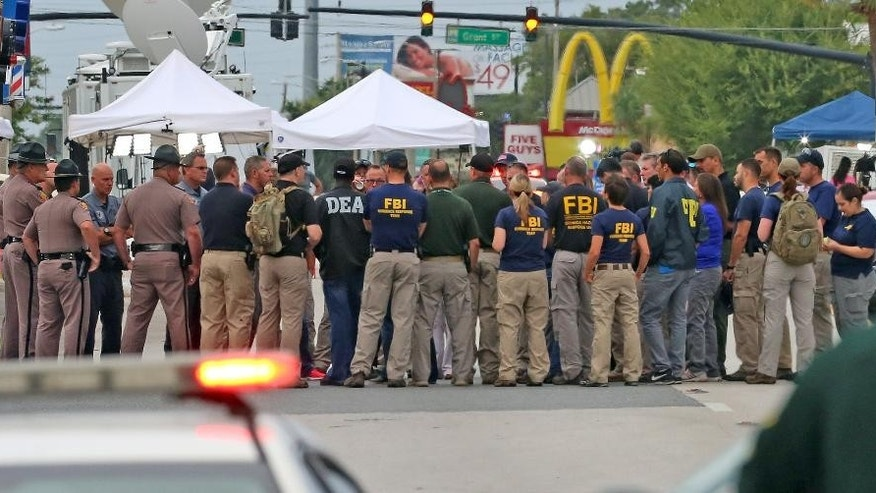 Multiple law enforcement agencies gather early Monday, June 20, 2016, in front of  Pulse Nightclub at the mass shooting scene in Orlando. Federal investigators promised to provide more insight as to what was happening inside the Pulse nightclub after a gunman started a deadly assault that was the worst mass shooting in modern U.S. history.  (Red Huber/Orlando Sentinel via AP)