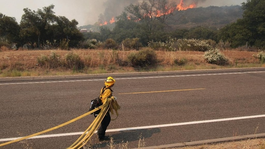 A firefighter pulls out a hose as a wildfire approaches Highway 94near Potrero, Calif., on Monday, June 20, 2016. (Hayne Palmour IV/San Diego Union-Tribune via AP)