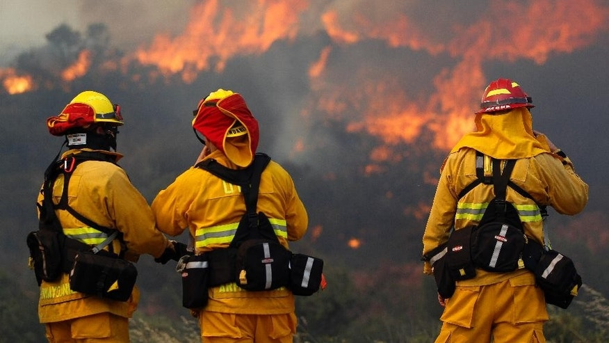 Upland firefighters, from left, Nima Homayounieh, Joseph Armendariz, and Capt. Joe Burna, watch as flames burn toward Highway 94 near Potrero, Calif., on Monday, June 20, 2016. (Hayne Palmour IV/San Diego Union-Tribune via AP)