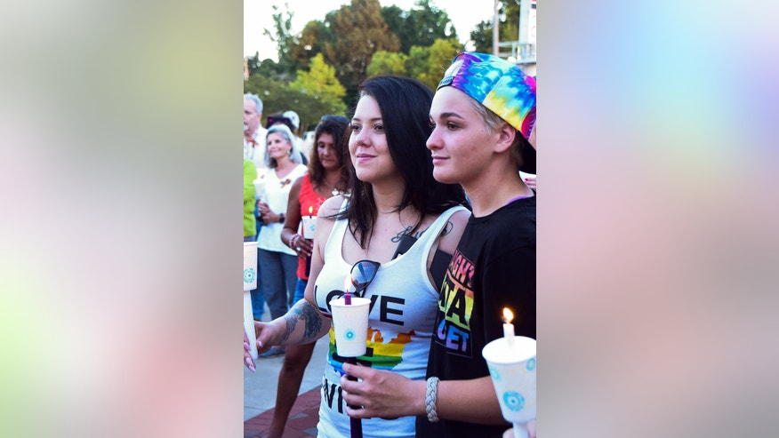 Samantha Sharrah and her sister Shauna Noumi,16, comfort each other at the Orlando Vigil, in honor of the of the victims of the Pulse Nightclub shooting on June 12, 2016,  held at the Freedom Fountain in downtown Jacksonville, N.C., on Sunday, June 19, 2016. (Elizabeth Horn/The Jacksonville Daily News via AP) MANDATORY CREDIT