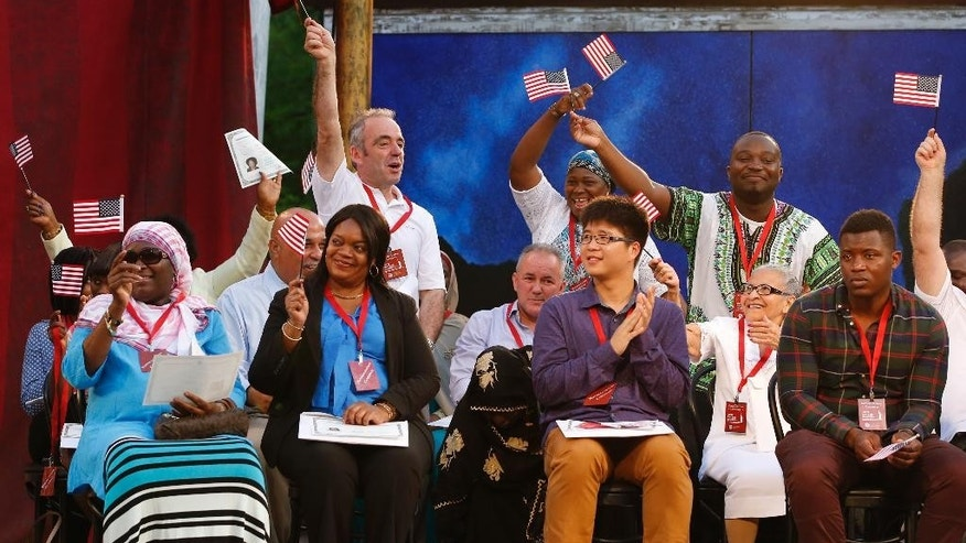 New U.S. citizens from a dozen countries including Albania, Benin, Cameroon, China, Cuba, Gambia, Guinea, Jamaica, Kosovo, Liberia, Mali and Nigeria celebrate on stage after they took an oath of allegiance and pledged allegiance to the flag of the United States during a U.S. naturalization ceremony on World Refugee Day at the Delacorte Theater in Central Park, Monday, June 20, 2016, in New York. The special ceremony was sponsored by the U.S. Department of Homeland Security, the International Rescue Committee, and the Public Theater. (AP Photo/Kathy Willens)