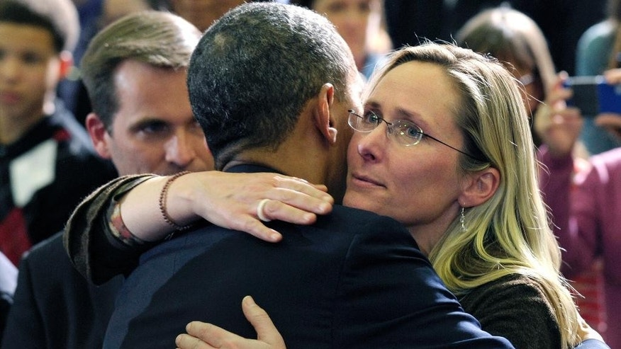 FILE - In this April 8, 2013, file photo, President Barack Obama embraces Scarlett Lewis, mother of Sandy Hook Elementary School shooting victim Jesse Lewis, after speaking at in Hartford, Conn. Through his death in a gun battle with police on Sunday, June 12, 2016, the Orlando nightclub gunman deprived his victims' families of the chance for a trial that could have helped to channel grief, offer a sense of justice or provide answers for the bloodshed. In Newtown, Conn., where the gunman took his own life after killing 26 people inside the school in December 2012, Lewis said his survival only would have made it more difficult as she grieved for her murdered son, Jesse. (AP Photo/Susan Walsh, File)