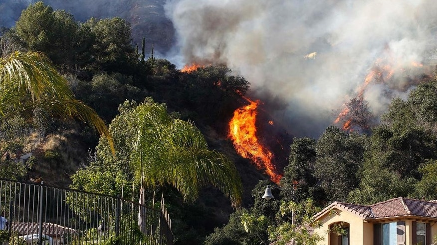 A wildfire burns around homes built near a hilltop in Azusa, Calif., Monday, June 20, 2016. New wildfires erupted Monday in Southern California and chased people from their homes as an intensifying heat wave stretching from the West Coast to New Mexico blistered the region. (AP Photo/Nick Ut)