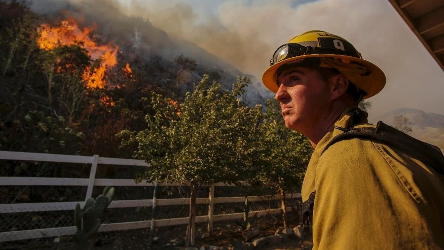 A firefighter keeps watch a wildfire in Azusa, Calif., Monday, June 20, 2016. New wildfires erupted Monday near Los Angeles and chased people from their suburban homes as an intense heatwave stretching from the West Coast to New Mexico blistered the region. (AP Photo/Ringo H.W. Chiu)