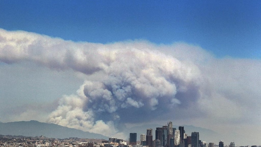 Smoke from wildfires burning in Angeles National Forest fills the sky behind the Los Angeles skyline on Monday, June 20, 2016. The wildfires several miles apart devoured hundreds of acres of brush on steep slopes above foothill suburbs erupted in Southern California as an intensifying heat wave stretching from the West Coast to New Mexico blistered the region with triple-digit temperatures. (AP Photo/Ringo H.W. Chiu)