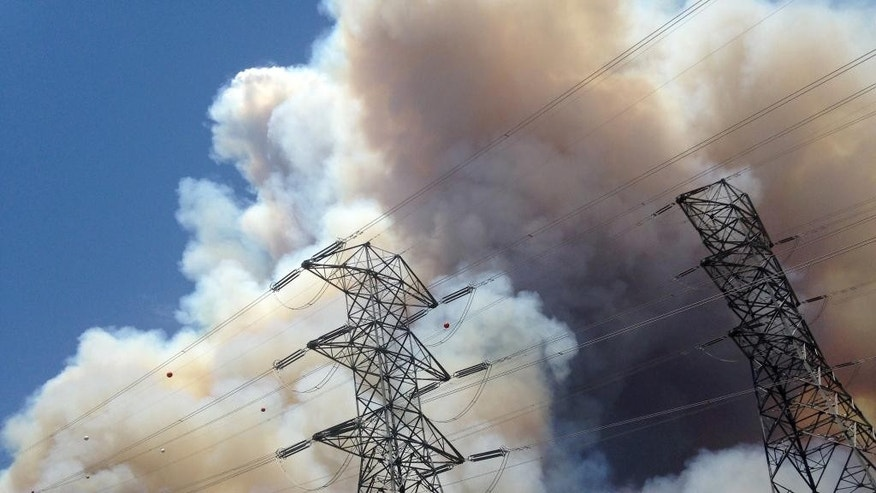 Smoke from a wildfire rises from a hillside near power lines outside of Azusa, Calif., Monday, June 20, 2016. Two fires have erupted in the San Gabriel Mountains northeast of Los Angeles amid withering heat. The first fire reported Monday was near Morris Reservoir north of suburban Azusa. AP Photo/Nick Ut)