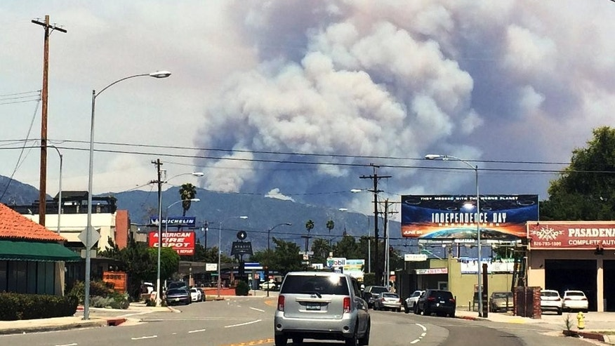 Towering columns of smoke rise from two wildfires on the San Gabriel Mountains are viewed from Pasadena, Calif., Monday, June 20, 2016. The wildfires several miles apart devoured hundreds of acres of brush on steep slopes above foothill suburbs erupted in Southern California as an intensifying heat wave stretching from the West Coast to New Mexico blistered the region with triple-digit temperatures. (AP Photo/Beth Harris)