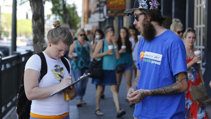 In this June 11, 2016 photo, Damian Riniker, right, a marijuana reform advocate with the group NORML, stands by while a passerby signs a petition to get a pot club initiative on the ballot in the next election, in Denver. Legal marijuana is giving Colorado a stinky conundrum. Visitors can buy the drug, but they can't use it in public. Or in a rental car. Or in most hotel rooms. Some legalization advocates believe they have a solution - pot clubs. (AP Photo/Brennan Linsley)