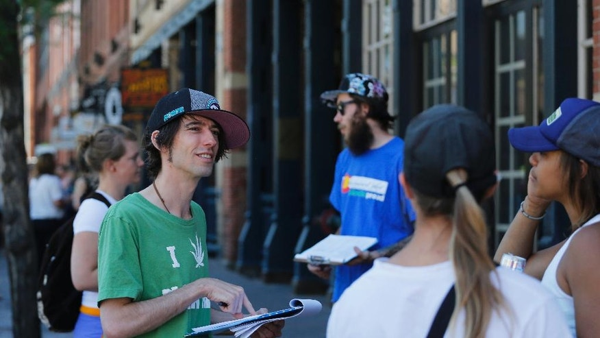 In this June 11, 2016 photo, Robert Cleary, left, a marijuana reform advocate with the group NORML, talks with passersby, gathering signatures on a petition to get a pot club initiative on the ballot in the next election, in Denver. Legal marijuana is giving Colorado a stinky conundrum. Visitors can buy the drug, but they can't use it in public. Or in a rental car. Or in most hotel rooms. Some legalization advocates believe they have a solution - pot clubs. (AP Photo/Brennan Linsley)