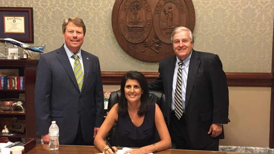 Haley (seated) signed the bill as Huggins, (l.), and former state Sen. Don Vaughan, (r.), looked on.