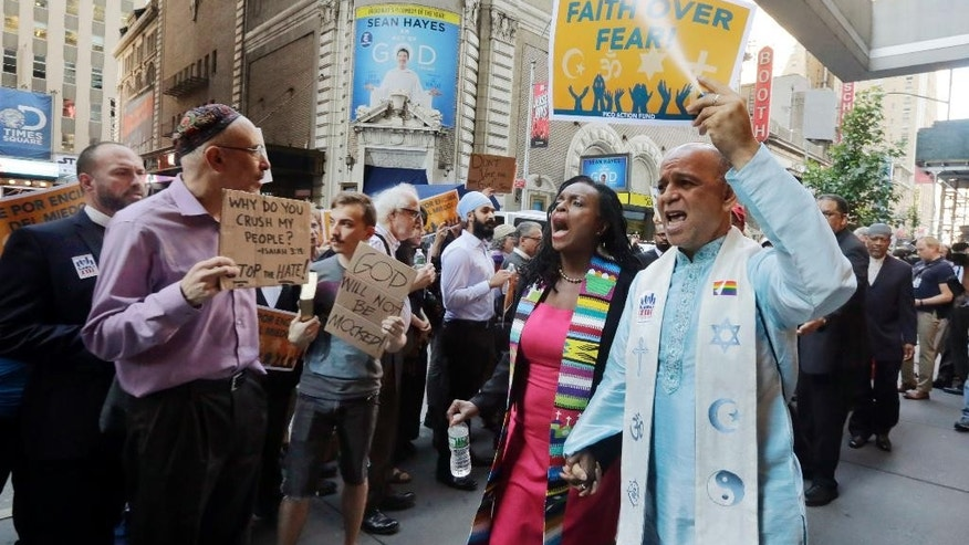 Clergy leaders with PICO (People Improving Communities through Organizing) Action Fund and their local federation, Faith in New York, demonstrate outside the hotel in New York's Times Square, Tuesday, June 21, 2016, where Republican presidential candidate Donald Trump is scheduled to meet evangelical clergy. (AP Photo/Richard Drew)