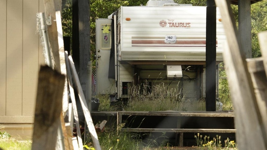 This photo shows a trailer where multiple people were found dead following a shooting Wednesday, June 22, 2016, in Lacey, Wash. Police have not yet determined a suspect or motive in the shooting. (AP Photo/Rachel La Corte)