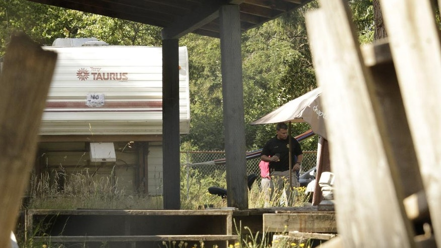 Investigators work outside of a travel trailer where multiple bodies were found Wednesday, June 22, 2016, in Lacey, Wash. Police have not yet determined a suspect or motive in the shooting. (AP Photo/Rachel La Corte)