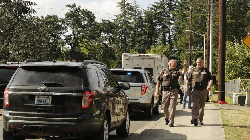 Officials with the Thurston County Sheriff's Office walk in a neighborhood where a shooting left multiple people dead Wednesday, June 22, 2016, in Lacey, Wash. Police have not yet determined a suspect or motive. (AP Photo/Rachel La Corte)