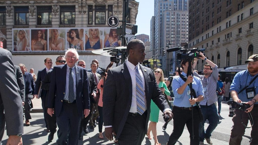 In this photo taken April 18, 2016, Democratic presidential candidate Sen. Bernie Sanders, I-Vt., is surrounded by reporters and Secret Service agents as he takes a walk in midtown Manhattan in New York. Being mathematically eliminated from the race to win the Democratic presidential nomination hasn't stopped apSanders from continuing his White House bid or be protected by a group of highly trained, costly Secret Service agents. (AP Photo/Mary Altaffer)
