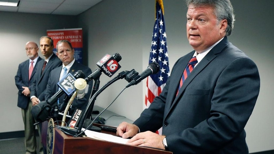 Federal agents, left, listen as Mississippi Attorney General Jim Hood tells reporters that the investigation is closed.