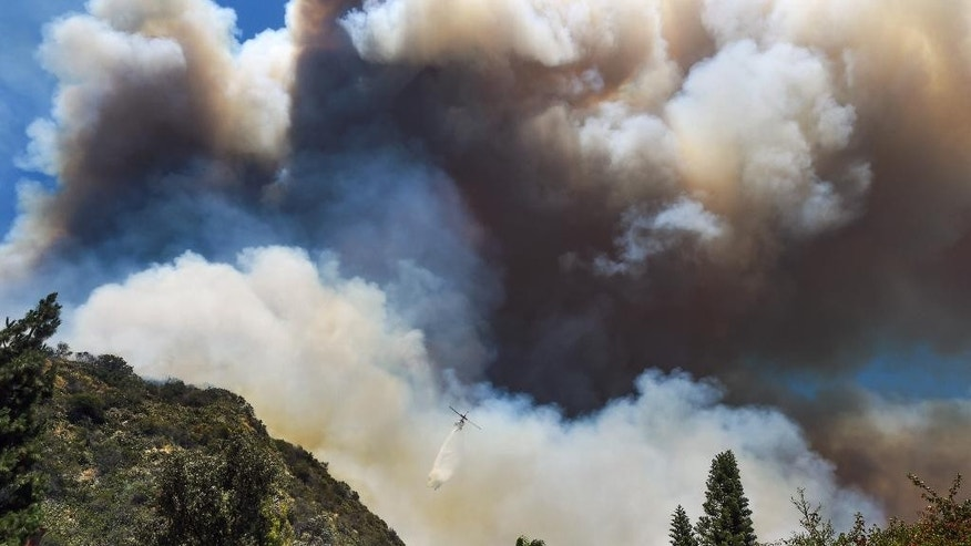 A helicopter drops water on a wildfire burning along the foothills in Duarte, Calif., Monday, June 20, 2016. (Walt Mancini/Pasadena Star-News via AP) MAGS OUT, NO SALES