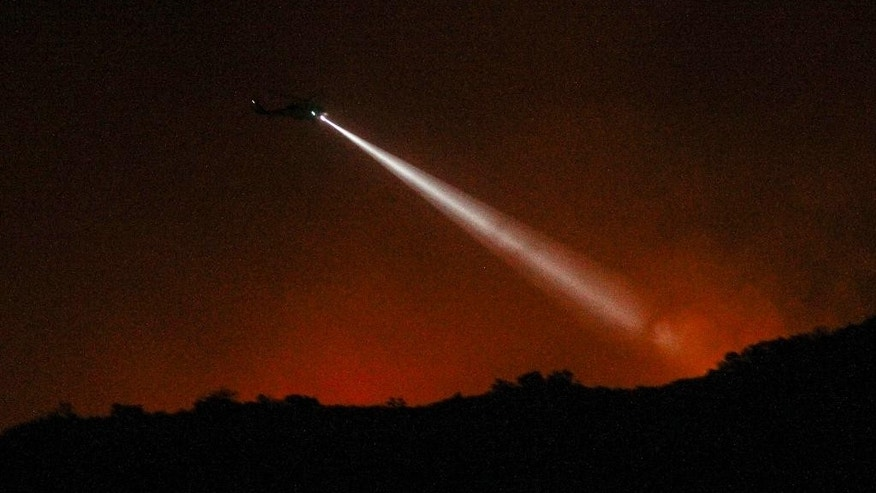 A firefighting helicopter prepares to make a water drop on a wildfire in Duarte, Calif., Tuesday, June 21, 2016. Firefighters worked to make gains against Southern California wildfires as an intense heat wave eased slightly Tuesday, but officials warned nearby communities to stay alert and obey any evacuation orders. (AP Photo/Ringo H.W. Chiu)