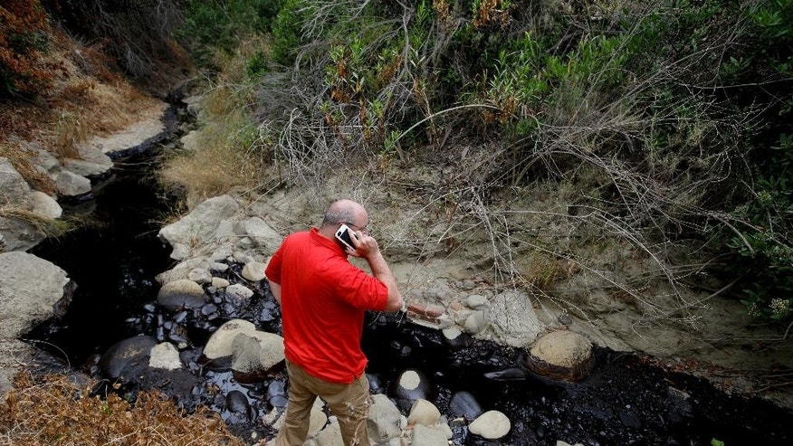 Cal State Channel Islands professor Sean Anderson talks on the phone as he studies oil from a spill Thursday, June 23, 2016, in Ventura, Calif. Thousands of gallons of crude oil spilled Thursday from a pipeline and flowed down an arroyo in Southern California.  (AP Photo/Jae C. Hong)