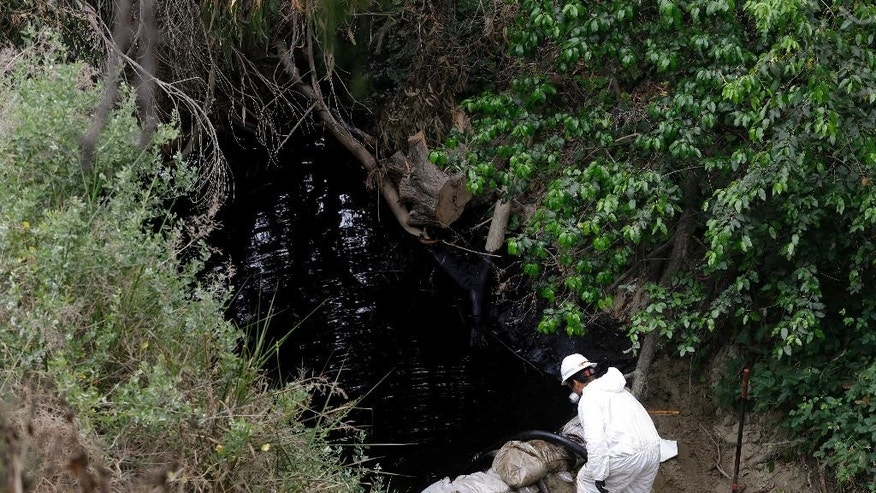 A worker vacuums oil from a spill, Thursday, June 23, 2016, in Ventura, Calif. Thousands of gallons of crude oil spilled Thursday from a pipeline and flowed down an arroyo in Southern California. (AP Photo/Jae C. Hong)