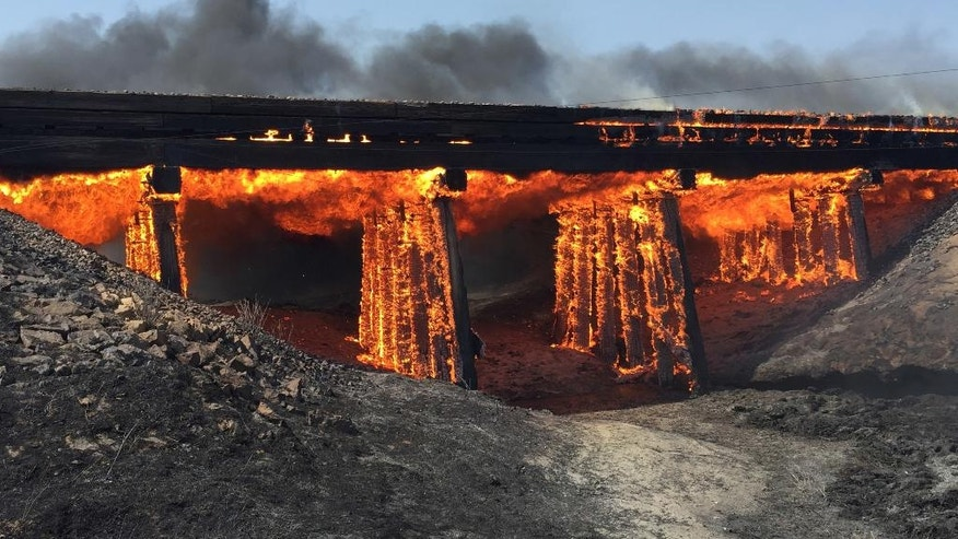 In this photo provided by Kiowa County, Colo., Sheriff Casey Sheridan, a railroad trestle burns near the tiny town of Haswell, Colo., Wednesday, June 22, 2016. For days, wildfires have raged amid spiking heat across Southern California and much of the West, forcing many to evacuate.   (Casey Sheridan/Kiowa County, Colo., Sheriffs Department via AP)