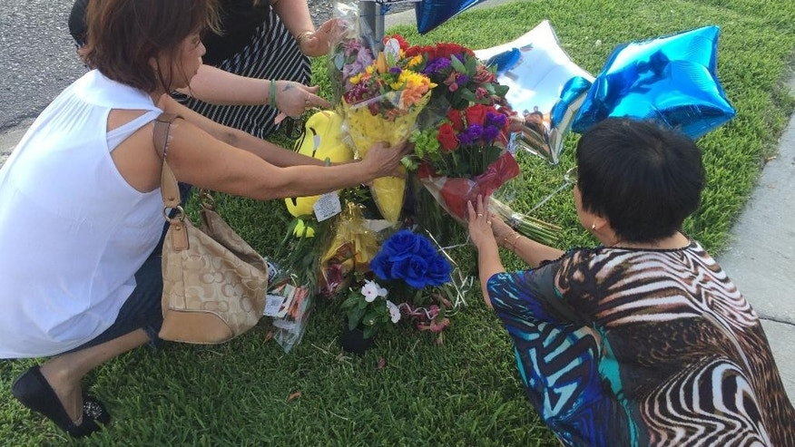 MonaLisa Urbina, rear, and two friends, Thuy Nguyen, front left, and Kim Pham, lay flowers at a memorial for Jefferson Parish Sheriff's Deputy David F. Michel Jr. in Harvey, La., Wednesday, June 22, 2016. A pedestrian walking down a busy commercial strip of the New Orleans suburb in the middle of the afternoon shot the sheriff's deputy multiple times, killing him, after being stopped by the officer Wednesday, an official said. (AP Photo/Cain Burdeau)
