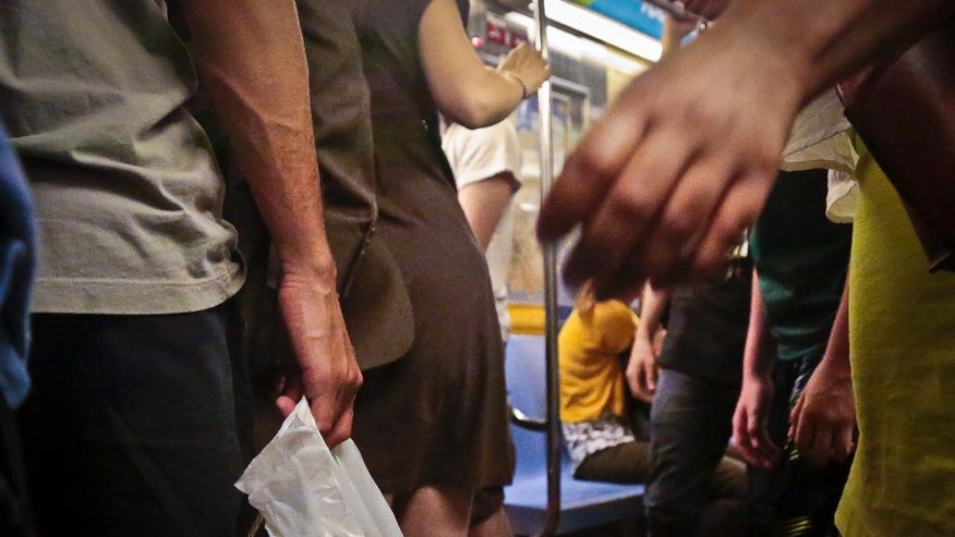 Subway riders board a train during rush hour, Wednesday, June 22, 2016, in New York. As subway ridership reaches an all-time record, police say reports of sex offenses underground are also on the rise, up nearly 57 percent from last year. (AP Photo/Bebeto Matthews)