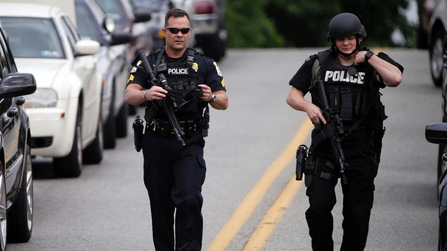 Law enforcement gather in the aftermath of a shooting, Friday, June 24, 2016, in Folcroft, Pa. Authorities are hunting for a suspect after a police officer was shot near Philadelphia. Amtrak spokesman Craig Schulz says two northbound passenger trains are being held due to the police activity in the area. (AP Photo/Matt Rourke)