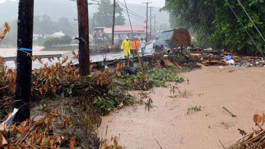 In this photo made from video, debris from the Jordan Creek near Clendenin, W.Va., piles up against a culvert along U.S. 119 on Thursday night June 23, 2016, just before the creek's entry into the Elk River. Multiple fatalities have been reported in flooding that has devastated parts of the state, a state official said Friday morning. (Chris Dorst/Gazette-Mail via AP)    MANDATORY CREDIT