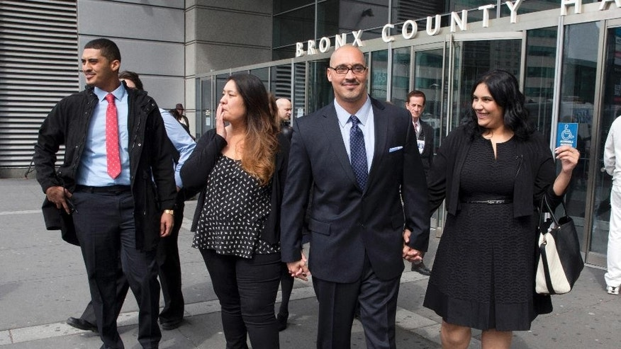 FILE- In this March 23, 2016 file photo, Richard Rosario, center, is joined by his daughter Amanda, right, son Richard Jr., left, and wife Minerva as he leaves Bronx state Supreme Court in New York after his conviction was overturned. Rosario, who spent 20 years in prison for a killing he says happened while he was in Florida asked a judge Friday, June 24, 2016 to keep his case open so he could be fully vindicated. (AP Photo/Mary Altaffer, File)