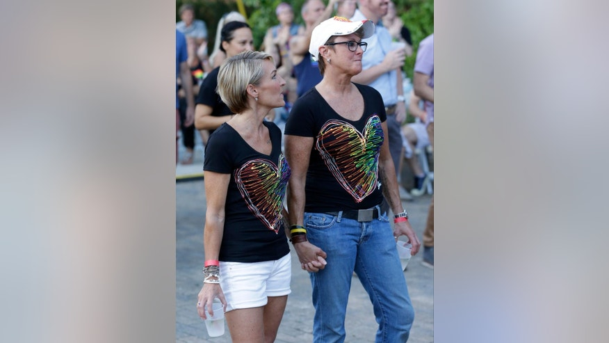 Pamela Sadlon, left, and Julie Eberwein attend a street party, Thursday, June 23, 2016, in Orlando, Fla., to benefit the employees of the Pulse nightclub, the scene of the recent mass shooting. (AP Photo/John Raoux)
