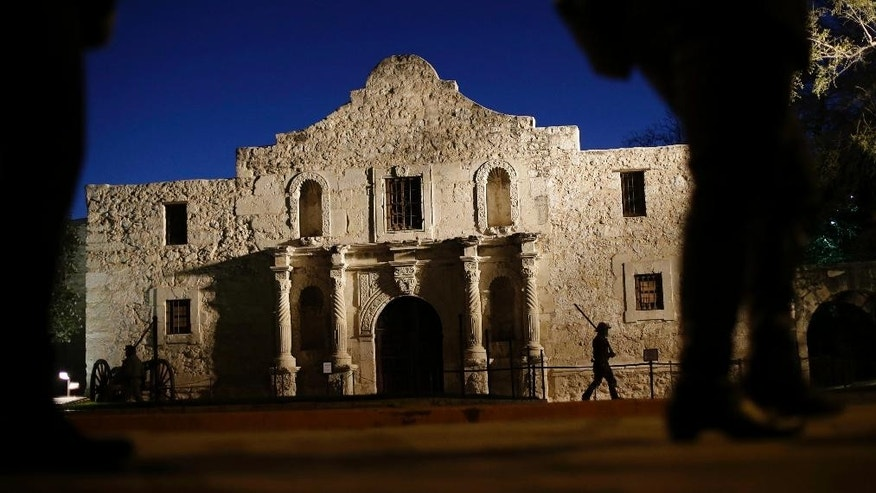 FILE - In this March 6, 2013, file photo, Dan Phillips, a member of the San Antonio Living History Association, patrols the Alamo during a pre-dawn memorial ceremony to remember the 1836 Battle of the Alamo and those who fell on both sides, in San Antonio. The Daughters of the Republic of Texas, a group that served as guardian of the Alamo for more than a century and the Texas General Land Office, reached a settlement Friday, June 24, 2016, in a dispute over ownership of about 38,000 books and artifacts that had been kept at the Texas shrine. (AP Photo/Eric Gay, File)