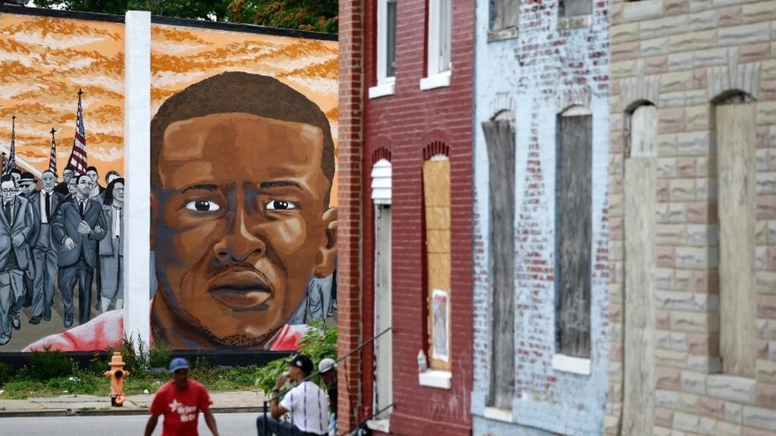 A mural depicting Freddie Gray is seen past blighted row homes in Baltimore, Thursday, June 23, 2016, at the intersection where Gray was arrested. Officer Caesar Goodson, one of six Baltimore city police officers charged in connection to the death of Gray, was acquitted of all charges in his trial Thursday. (AP Photo/Patrick Semansky)