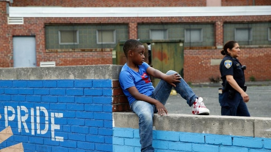 A boy sits on a wall as a member of the Baltimore Police Department walks by in the Penn North neighborhood of Baltimore, Thursday, June 23, 2016, near the site of unrest following the funeral of Freddie Gray. Officer Caesar Goodson, one of six Baltimore city police officers charged in connection to the death of Gray, was acquitted of all charges in his trial Thursday. (AP Photo/Patrick Semansky)