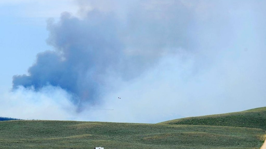 A cloud of smoke rises over the site of a forest fire near Walden, Colo., on Wednesday, June 22, 2016. A shift in the wind turned the blaze, which is burning in a heavily-wooded area with no permanent residents, into a fast-moving threat that has forced campers to evacuate from the area near the Colorado-Wyoming border. Trees killed by a beetle infestation are fueling the flames at the site, which is 140 miles north and west of Denver. (Matt Stensland/Steamboat Pilot & Today via AP)