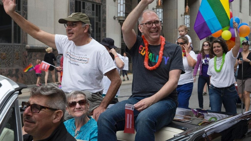 """FILE - In this June 27, 2015, file photo, gay marriage plaintiff Jim Obergefell, center, waves during the Cincinnati Pride parade in Cincinnati. Obergefell asked his longtime partner John Arthur, dying from ALS, to marry him on June 26, 2013, leading to Obergefell's name appearing at the top of the U.S. Supreme Court's June 26, 2015, decision that legalized same-sex marriage nationwide. Obergefell is co-author of a book published June 14, 2016, titled """"Love Wins: The Lovers and Lawyers Who Fought the Landmark Case for Marriage Equality."""" (AP Photo/John Minchillo, File)"""